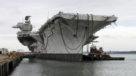 """In this photo released by the U.S. Navy, a tugboat works alongside the decommissioned aircraft carrier USS Saratoga on Thursday, August 21, in Newport, Rhode Island. The Navy has paid a Texas recycling company a penny to dispose of the Saratoga, part of the Forrestal-class of """"supercarrier"""" vessels built for the Atomic Age. The carrier was decommissioned 20 years ago."""