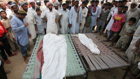 Indian villagers gather near the bodies of those killed in cross-border firing between Indian and Pakistani forces in Kashmir