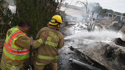 Napa County firefighters spray foam on hot spots from a fire at a mobile home park after an earthquake Sunday.
