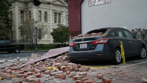 Bricks from a damaged building sit atop a car on August 24 in Napa.