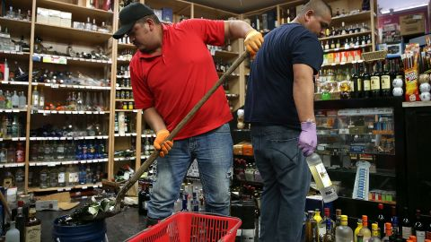Eddie Villa, left, and Jesus Villa clean up broken bottles at Van's Liquors  August 24 in Napa.
