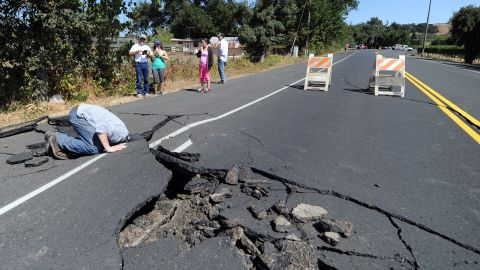 Nicholas George looks under a buckled highway just outside of Napa on August 24.