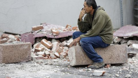 Ron Peralez sits on rubble and looks at damaged buildings on Monday, August 25, in Napa, California. The San Francisco Bay Area's strongest earthquake in 25 years struck the heart of California's wine country on August 24.
