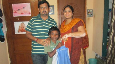 """Abhilekha Rampuria (right) gives a boy, Balaji, 5kgs of rice. She says: """"He has 2 siblings. His mother works as housemaid. They buy daily 1/2kg of rice to serve their hunger needs. He does not have a father. Still they don't beg."""""""