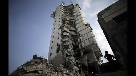 Palestinians inspect the damage to a residential building following several late night Israeli airstrikes in Gaza City on August 26.