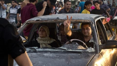 A Palestinian man flash the sign of victory through the shatered front window of his battered car as he makes his way through an intersection in Gaza City where people gather to celebrate the ceasefire between Israel and Hamas on August 26, 2014. Egypt said that a Gaza ceasefire that went into force at 1600 GMT provides for an immediate opening of Israeli border crossings to aid and reconstruction supplies. AFP PHOTO/ROBERTO SCHMIDT (Photo credit should read ROBERTO SCHMIDT/AFP/Getty Images)