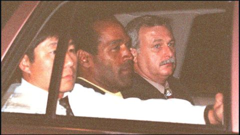 O.J. Simpson, accompanied by two Los Angeles police detectives, is driven away after his arrest.