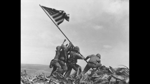 U.S. Marines of the 28th Regiment, 5th Division, raise the American flag atop Mount Suribachi, Iwo Jima, on February 23, 1945. Strategically located only 660 miles from Tokyo, the Pacific island was essential to launching land-based bombers against Japan. It was the bloodiest battle in the history of the U.S. Marine Corps, which suffered more than 27,000 casualties. Of some 18,000 Japanese soldiers defending the island, 216 survived.