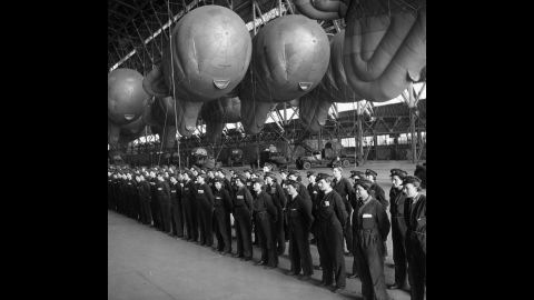 """Balloon operators from Britain's Women's Auxiliary Air Force, or WAAF, report for inspection in a hangar used to store balloons, at a facility in the UK. During World War II, women played a significant role in the war effort. They took jobs in """"defense plants and volunteered for war-related organizations, in addition to managing their households,"""" according to the World War II museum in New Orleans."""