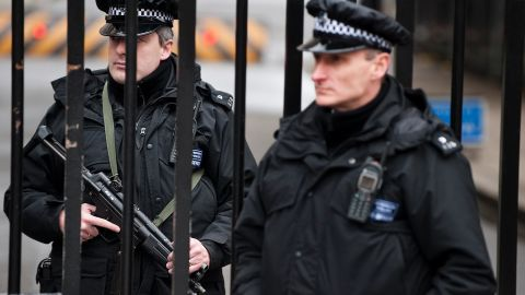 Armed policemen stand guard at the gates of Downing Street in London.
