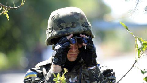 A member of Ukrainian volunteer battalion Dnipro looks through binoculars near the small southern Ukrainian city of Novoazovsk, Donetsk region, on August 27, 2014.