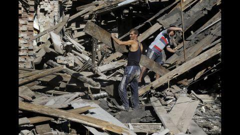 Men clear rubble in Ilovaisk, Ukraine, on Sunday, August 31.