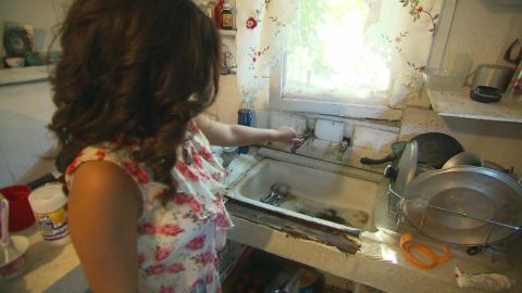 Sandra Tapia uses a hose hookup to a neighbor's house to wash dishes.