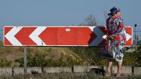 A woman stands next to a road sign September 7 after an overnight bombing attack at an Ukrainian army checkpoint on the outskirts of Mariupol.