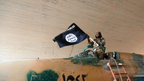 FILE - This undated file image posted on Aug. 27, 2014, by the Raqqa Media Center of the Islamic State group, a Syrian opposition group, which has been verified and is consistent with other AP reporting, shows a fighter of the Islamic State group waving their flag from inside a captured government fighter jet following the battle for the Tabqa air base, in Raqqa.