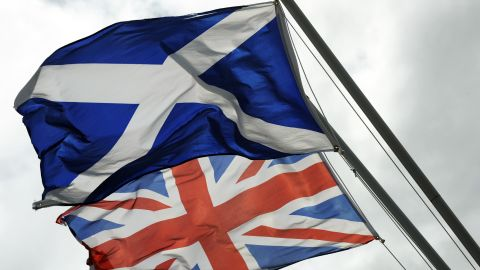Caption:The Saltire, the flag of Scotland flies above the Union flag at the site of the Auld Acquaintance cairn which is being constructed at a site on the banks of the River Sark in Gretna in Scotland, which is thought to be the historic border between Scotland and England, taken on August 17, 2014. A month to the day until Scotland votes on whether to split from Britain, opinion polls Monday showed the pro-independence camp gaining ground as First Minister Alex Salmond insisted his side had a 'spring in their step'. But the polls still showed a strong lead for the 'No' camp ahead of the vote on September 18, suggesting voters are on course to reject independence. Debate in the campaign has so far focused on Scotland's economy, particularly on the currency post-independence. AFP PHOTO/ANDY BUCHANAN (Photo credit should read Andy Buchanan/AFP/Getty Images)