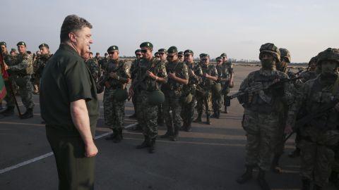 Ukrainian President Petro Poroshenko, left, inspects military personnel during a visit to Mariupol on Monday, September 8.