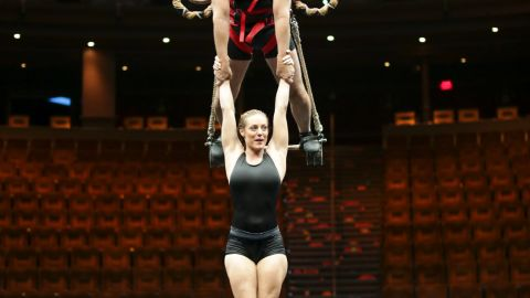 """Rowe holds performer Chelsea Bakken above the pool at the Las Vegas water acrobatic show """"Le Reve."""""""