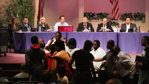 FERGUSON, MO - SEPTEMBER 09:  Mayor James Knowles (seated R) ) and city council members wait until angry residents are calmed down during the Ferguson city council meeting on September 9, 2014 in Ferguson, Missouri. The meeting was held at Greater Grace Church to accommodate the large crowd. Most residents used the meeting to express their anger at how the police and city council handled the shooting of teenager Michael Brown and the unrest that followed.  (Photo by Scott Olson/Getty Images)