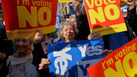 """GLASGOW, SCOTLAND - SEPTEMBER 10: """"Yes"""" and """"No"""" voters protest as John Prescott and Alistair Darling join the Scottish Labour Battle Bus on Rutherglen main street on September 10, 2014 in Glasgow, Scotland. The three UK party leaders are all campaigning in Scotland today showing their support for a """"No"""" vote in the independence referendum. (Photo by Mark Runnacles/Getty Images)"""