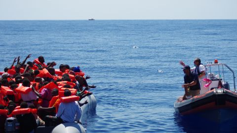 """A lifeboat from rescue ship """"Phoenix"""" approaches refugees, offering drinking water. """"We never approach a boat with our boat because it's rather big, so we approach cautiously with a dingy. The first thing we do is start giving out life jackets,"""" said MOAS director Martin Xuereb."""