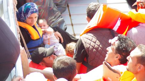 """Refugees receive help from rescue boat """"Phoenix."""""""