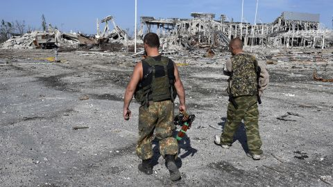 Armed pro-Russian rebels walk September 11 in front of the destroyed Luhansk International Airport. The rebels took control of the airport on September 1 after heavy fighting with the Ukrainian army.