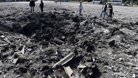 People look at a large crater from a reported missile strike that hit a bus station Friday, September 12, in Makiivka, Ukraine.