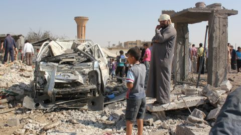 Syrian civilians stand at the site where a Syrian government forces aircraft fell after it was shot down by militants of the Islamic State (IS) group over the Syrian town of Raqa on September 16, 2014. The plane crashed into a house in the Euphrates Valley city, the sole provincial capital entirely out of Syrian government control, causing deaths and injuries on the ground,  Syrian Observatory for Human Rights monitoring group said. AFP PHOTO/RMC/STR        (Photo credit should read )