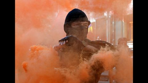 A protester holds a smoke bomb during a demonstration outside the Presidential Palace in Kiev, Ukraine, on September 17. Activists protested the adoption of legislation giving greater autonomy to rebel-held parts of eastern Ukraine's Donetsk and Luhansk regions.