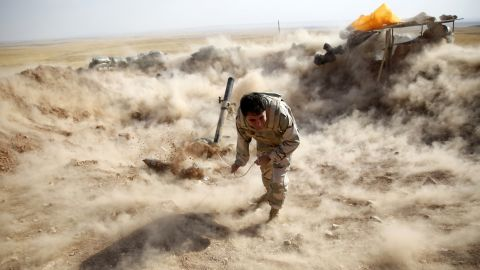 A Kurdish Peshmerga fighter launches mortar shells toward ISIS militants in Zumar, Iraq, on Monday, September 15.