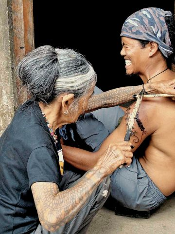 Whang-ud, who was 92 years old when this picture was taken in 2012, has been described as the last traditional tattooist in the Philippines. In recent years, enthusiasts and tourists have hiked for hours to reach the remote village in which she practices.