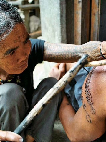 Whang-ud, 92, uses a lemon thorn attached to a wand to make these traditional tattoos.