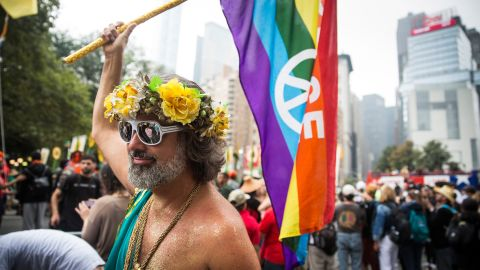 A man waves a rainbow flag as he marches in New York.
