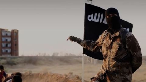 """An ISIS fighter who speaks perfect English with a North American accent is shown orchestrating the mass execution of a group of men in an ISIS recruitment video called """"Flames of War."""""""