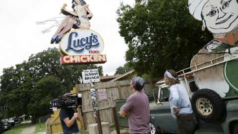 """Evan Voyles shows Rowe the sign he made for """"Lucy's Fried Chicken."""" Volyes runs """"The Neon Jungle,"""" a sign making business in Austin, Texas."""