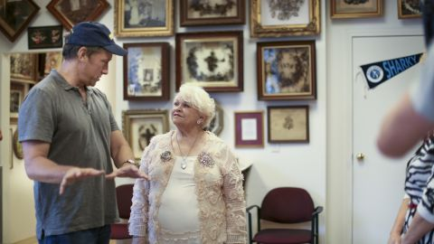 """Rowe talks with Leila Cohoon at her hair art museum in Missouri. """"Leila's Hair Museum"""" displays more than 600 wreaths and 2,000 pieces of jewelry made from human hair. The practice was popular in the Victorian era."""