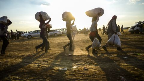 Syrian Kurds carry belongings as they cross the border between Syria and Turkey near Suruc, Turkey, on September 20.