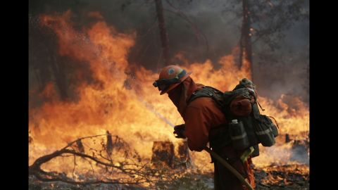 A firefighter hoses down hot spots during a controlled burn to fight the King Fire near Placerville, California, on Monday, September 22.
