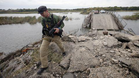 A pro-Russian rebel guards a destroyed bridge in Nyzhnya Krynka, Ukraine, on Tuesday, September 23.