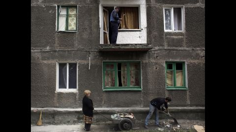 Residents clean up debris at a building damaged by rockets in Debaltseve, Ukraine, on Monday, September 22.