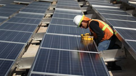 LAKEWOOD, CO - OCTOBER 01: A woker finishes installing solar panels funded by federal stimulus funds atop a government building on October 1, 2010 in Lakewood, Colorado. The $787 billion economic stimulus package U.S. President Barack Obama pushed through Congress last year is coming in on time and under budget according to a White House report released Friday. (Photo by John Moore/Getty Images)
