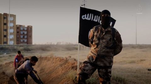 """An ISIS fighter, who speaks perfect English with a North American accent, is shown orchestrating the mass execution of a group of men in an ISIS recruitment video called """"Flames of War""""."""