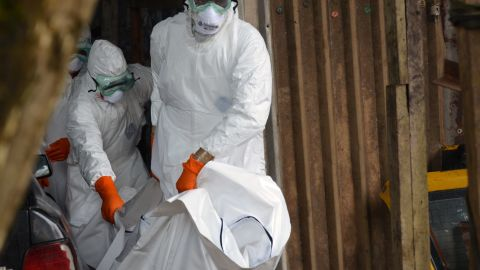 Liberian Red Cross health workers wearing protective suits carry the body of a victim of the Ebola virus out of a garage on September 10, 2014 in a district of Monrovia.
