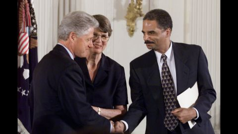 Holder shakes hands with then-President Bill Clinton as Attorney General Janet Reno, Holder's boss, looks on at an American Bar Association event at the White House in 1999.