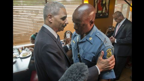 U.S. Attorney General Eric Holder talks with Capt. Ron Johnson, right, of the Missouri State Highway Patrol on August 20, 2014 in Ferguson, Missouri.
