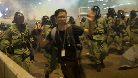 Demonstrators disperse as tear gas is fired by police.