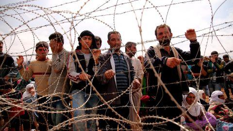 Syrian Kurds wait behind border fences to cross into Suruc on Sunday, September 28.