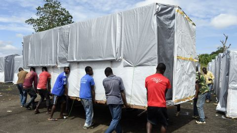 Workers move a building into place as part of a new Ebola treatment center in Monrovia on September 28, 2014.