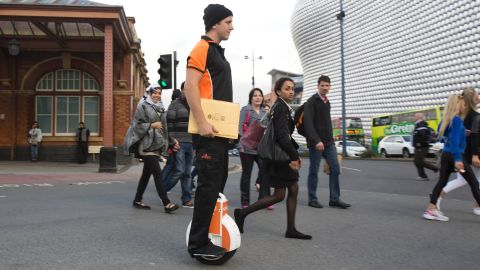 """A """"postie"""" trials the Airwheel unicycle in Birmingham. The company says the devices are now becoming popular with urban commuters."""